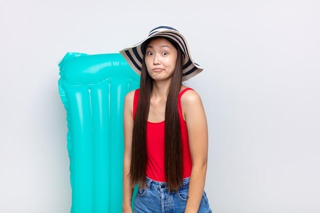 Азиатская молодая женщина с тупым, сумасшедшим, удивленным выражением лица, надутыми щеками, чувствуя себя набитой, жирной и полной еды