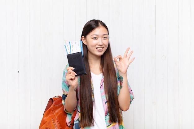 パスポートを持つアジアの若い女性。休日の概念