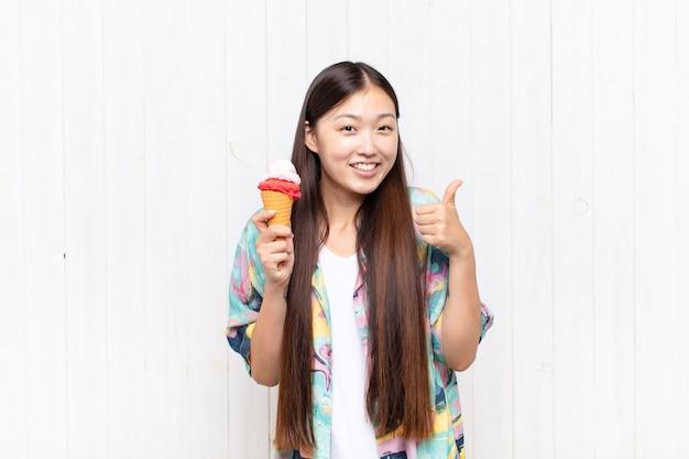 孤立したアイスクリームを持つアジアの若い女性
