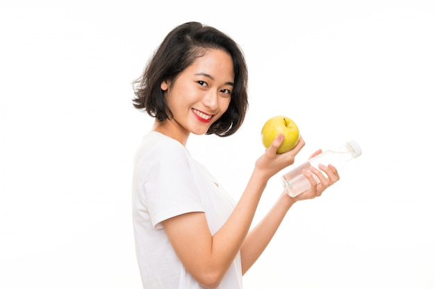 Asian young woman with an apple and bottle of water