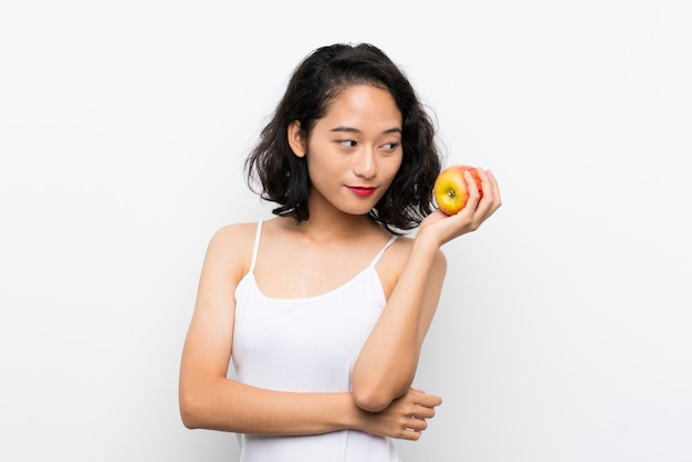 Asian young woman with an apple over isolated white background