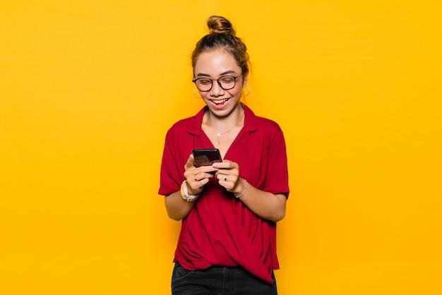 幸せそうな顔とスマートフォンを保持しているアジアの若い女性
