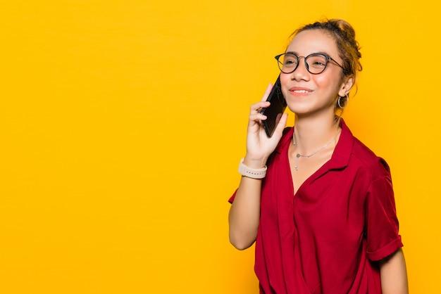 スマートフォンで話している幸せそうな顔を持つアジアの若い女性