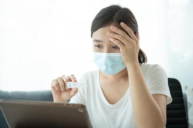 Sars 2019-ncov covid-19 코로나바이러스 항원 신속 검사 키트를 사용하여 위생 보호용 안면 마스크를 쓴 아시아 젊은 여성 - 집에서 ag 검사 키트를 사용하고 화상 통화를 통해 의사와 검사 결과를 상담합니다.