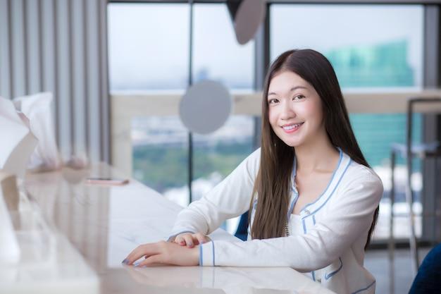 긴 머리를 한 아시아 젊은 여성이 유리 건물이 있는 직장의 의자에 앉아 있는 동안 미소를 짓습니다.