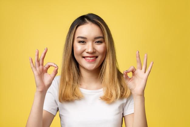 Okサインジェスチャーでアジアの若い女性