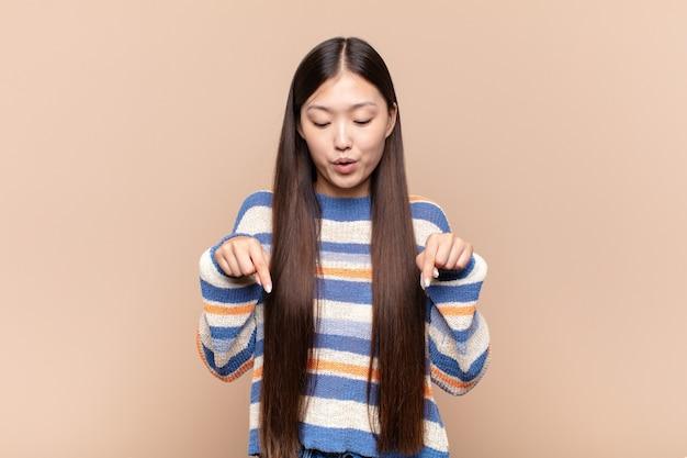 두 손으로 아래쪽을 가리키는 오픈 입으로 아시아 젊은 여자, 충격, 놀라움과 놀란 찾고