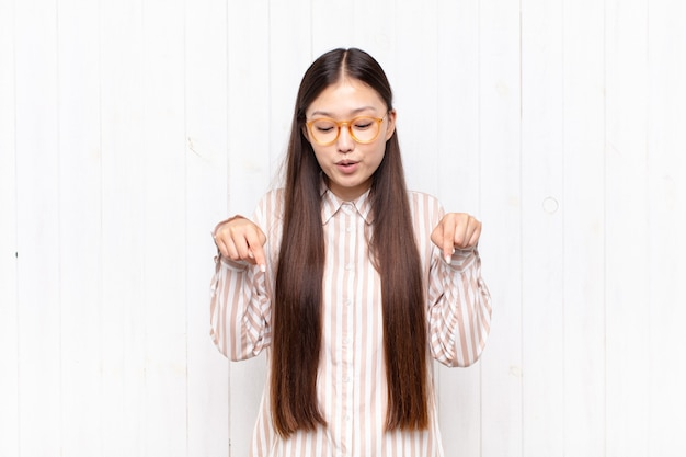 Asian young woman with open mouth pointing downwards with both hands, looking shocked, amazed and surprised