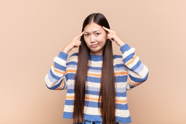 Asian young woman with a serious and concentrated look, brainstorming and thinking about a challenging problem