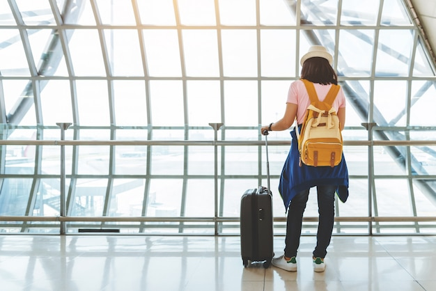 Asian young woman with suitcase and yellow backpack waiting for the flight at window of the airport.