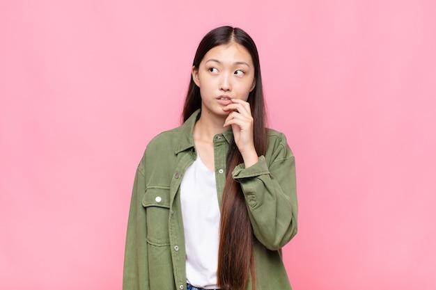 Азиатская молодая женщина с удивленным, нервным, встревоженным или испуганным взглядом смотрит в сторону в сторону копии пространства