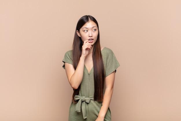 驚いた、緊張した、心配した、またはおびえた表情のアジアの若い女性