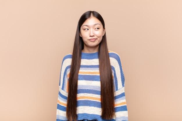 Азиатская молодая женщина задается вопросом, думает о счастливых мыслях и идеях, мечтает, ищет, чтобы скопировать пространство на стороне