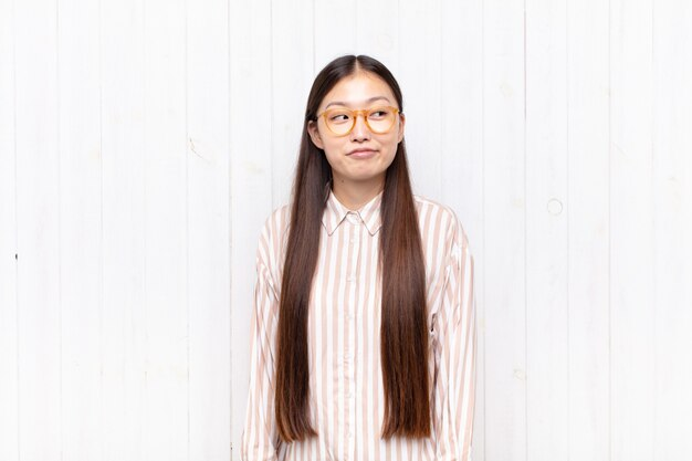 Asian young woman wondering, thinking happy thoughts and ideas, daydreaming, looking to copy space on side