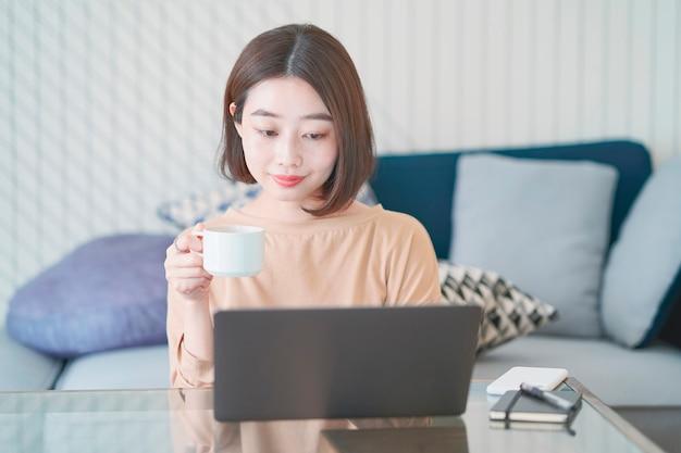 自宅の部屋でリモートで作業してアジアの若い女性