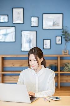カジュアルな部屋でラップトップで働くアジアの若い女性