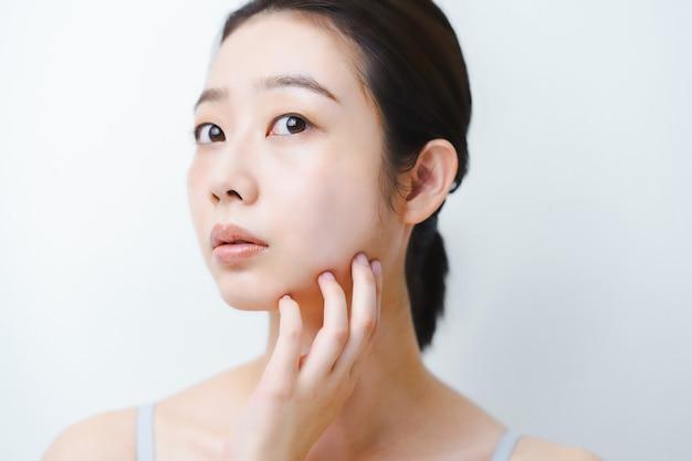 Азиатская молодая женщина беспокоится о состоянии кожи