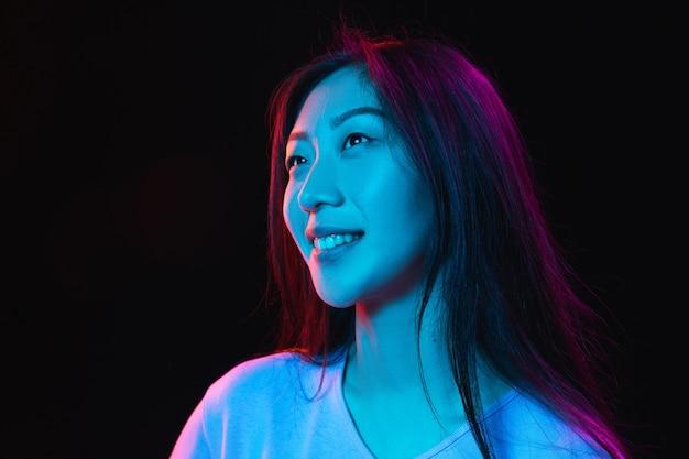 Портрет азиатской молодой женщины на темной стене в неоновой концепции человеческих эмоций, выражение лица, молодежная реклама