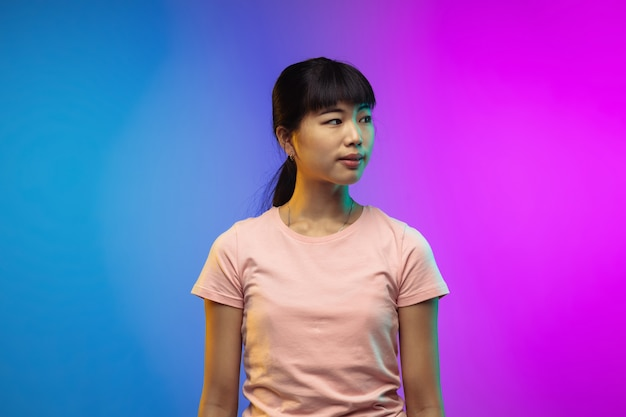 ネオンのグラデーションスタジオの背景にアジアの若い女性の肖像画