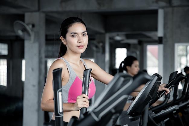 アジアの若い女性が笑顔でジムのエクササイズマシンで有酸素運動をしています。