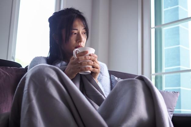 アジアの若い女性は気分が悪く、頭痛と高熱があります。病気の人の概念