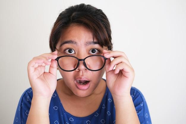 眼鏡を外しながらショックを受けた表情を見せているアジアの若い女性