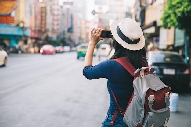 Азиатские молодые женщины фотографируют с мобильным путешествующим по фонету рюкзаком в yaowarat road.