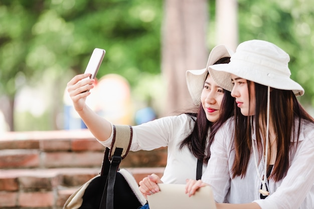 Asian young women tourists taking a selfie in city