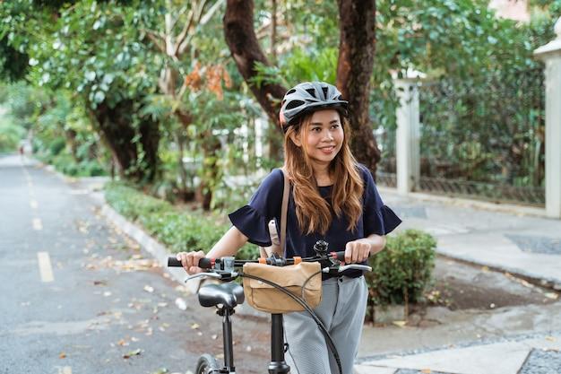 Asian young women walk on folding bikes