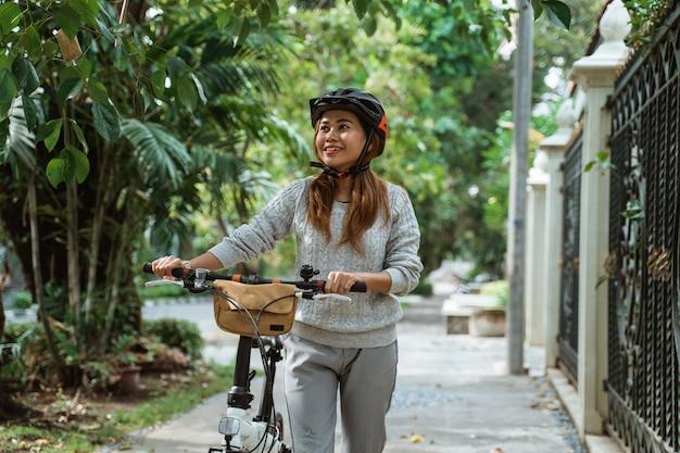 アジアの若い女性が折りたたみ自転車で歩く
