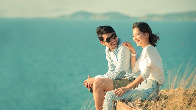 海側でリラックスしたアジアの若いカップル