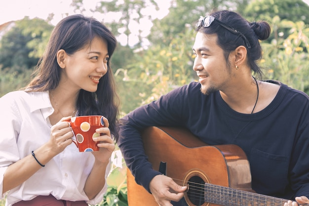Asian younger man and woman playing guitar singing song in park