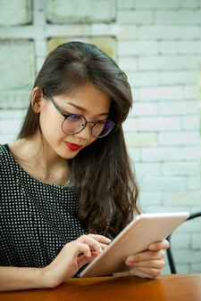 Asian younger woman reading message on computer tablet