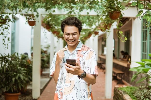 携帯電話を持って見ているアジアの若者はとても幸せです