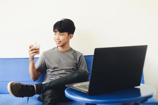 コーヒーを飲みながらノートパソコンの前のソファに座っているアジアの若者