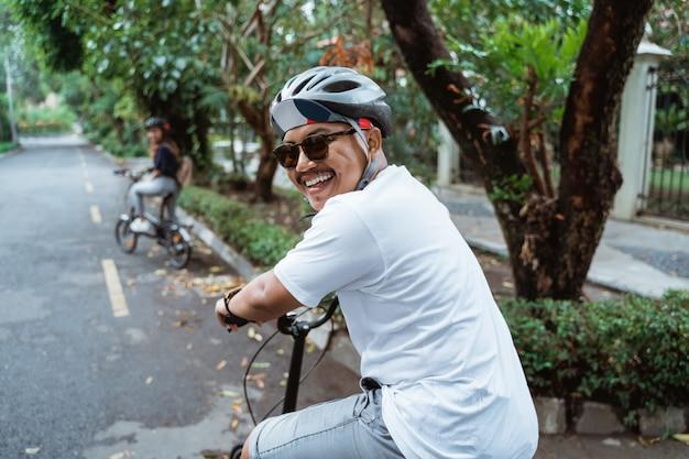 路上で自転車に乗るときアジアの若者は振り返って笑顔