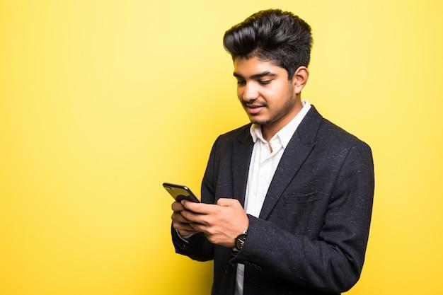 노란색 벽에 스마트 휴대 전화를 사용하는 asianindian 비즈니스 남자 잘 생긴 남자