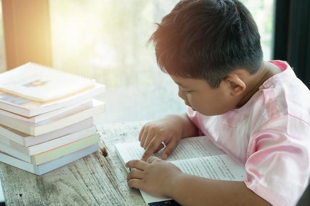 アジア人の少年は本を家で読んだ。教育コンセプト