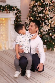 Asians dad and son laugh, smile and hug by the fireplace and christmas tree at home