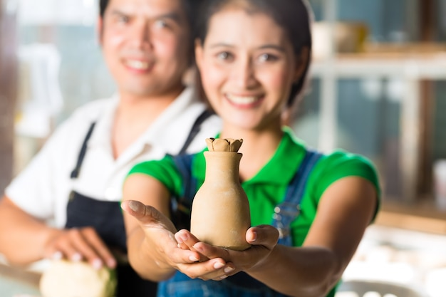 Asians with handmade pottery in clay studio
