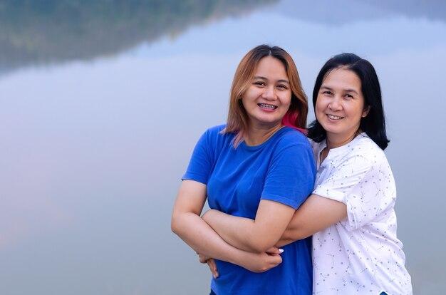 Азиатская мать и дочь обнимаются вместе на фоне озера