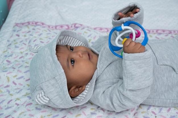 柔らかい毛布の上に横たわるかわいいasin男の子と遊ぶおもちゃ