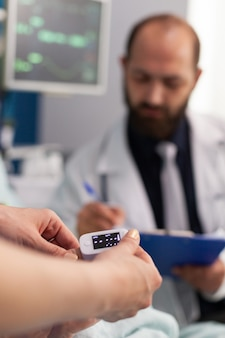 Asisstant nurse puts medical oximeter on finger while doctor man writes heartbeat puls rate