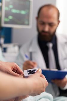 助手看護師が医療用酸素濃度計を指に置き、医師の男性が心拍脈拍数を書き込む