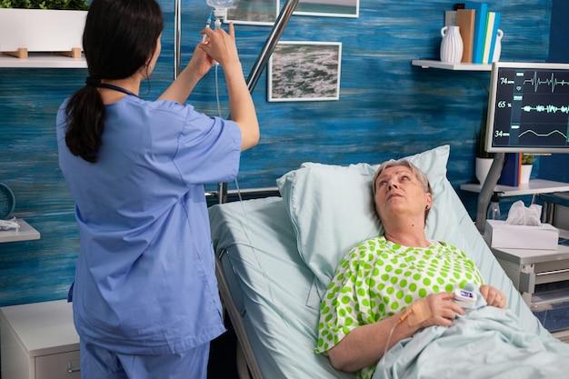 アシスタントの女性労働者が点滴バッグに治療を注入します