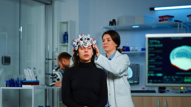 Помощь врача-невролога, надевающего наушники eeg на голову пациента, сканирование функций мозга, определение диагноза заболевания. команда ученых-исследователей работает поздно ночью в неврологической клинике
