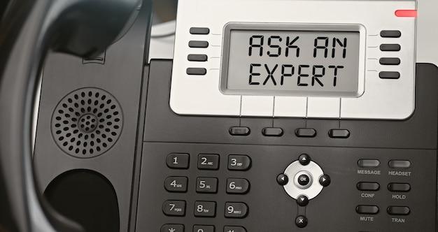 専門家に尋ねる-ip電話のディスプレイ上のテキストの概念。クローズアップip電話
