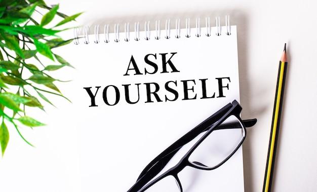 «спроси себя» написано в белой тетради рядом с карандашом, очками в черной оправе и зеленым растением.