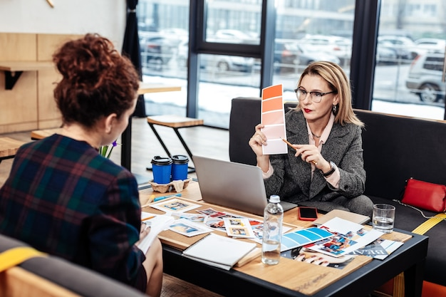 アドバイスを求めます。親切なアシスタントにアドバイスを求める眼鏡をかけた有名なプロのインテリア デザイナー