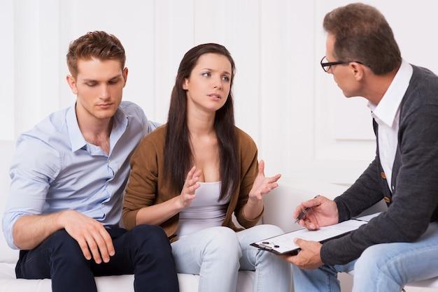 Просим совета специалиста. разочарованная молодая пара сидит на диване, пока женщина рассказывает психиатру о своих проблемах в отношениях и жестикулирует